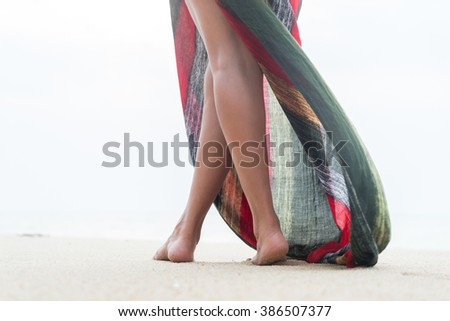Standing woman legs posing on the beach wearing a pareo  - stock photo