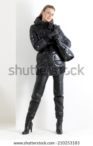 standing woman wearing black clothes holding a handbag - stock photo