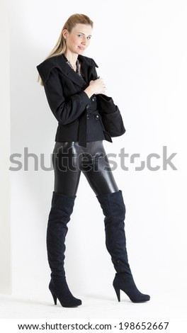 standing woman wearing black clothes with a handbag - stock photo