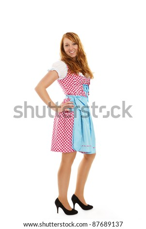 standing young redhead woman in bavarian dress on white background - stock photo