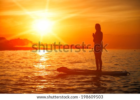 Standup paddle board yoga performed by beautiful girl on the bright sunset background, yoga training on the beach - stock photo
