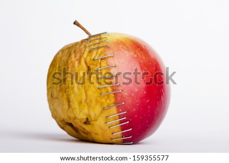 stapled two apple halves (young and old) as a metaphor for plastic surgery - stock photo