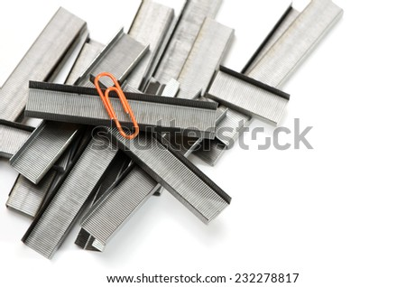 Stapler wires and orange paper clip as outstanding concept. - stock photo