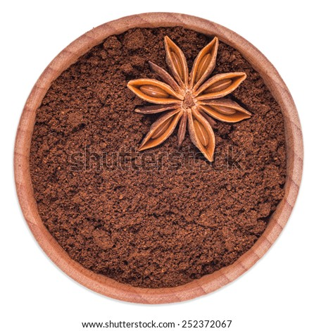 Star anise, ground coffee in a wooden bowl isolated on white background top view. - stock photo