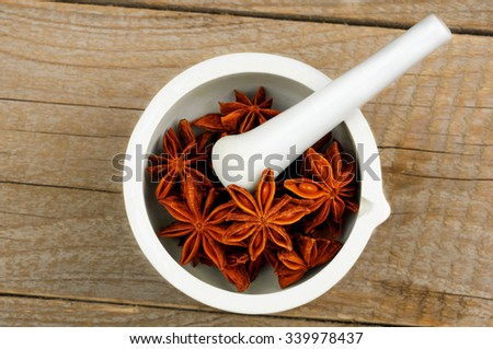 Star Anise in white mortar and pestle - stock photo