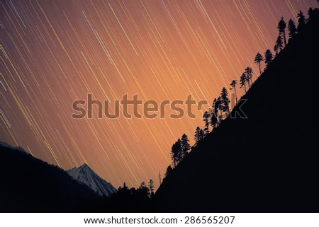 Star-fall. Stars seem to 'fall' down behind the hill creating beautiful star-rain with snowy Himalayan peak on the second plan. Nepal, ACAP, view from the Bagarchhap village (2,160 m) - stock photo