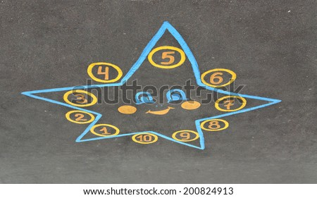 Star for game hopscotch drawn with chalk on the pavement - stock photo