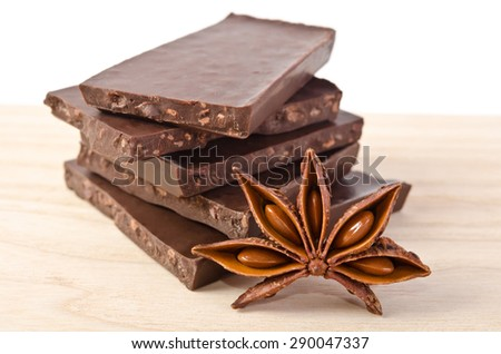 star of anise  and tower from chocolate  on wooden table - stock photo