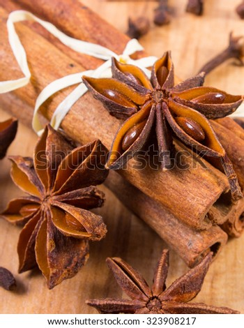 Star of anise, cinnamon sticks and cloves lying on wooden table, seasoning for cooking and baking - stock photo