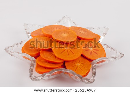 Star platter with sliced persimmons - side veiw - stock photo