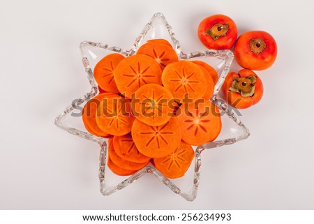 Star platter with sliced persimmons top view - stock photo