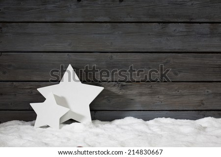 Star shaped christmas decoration on pile of snow against wooden wall - stock photo