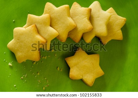 Star-shaped cookies on green plate - stock photo