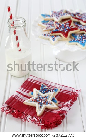 Star sugar cookies decorated for fourth of July celebration. Milk bottle with paper straw. - stock photo