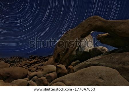 Star Trail Streaks over the Rocks of Joshua Tree Park - stock photo