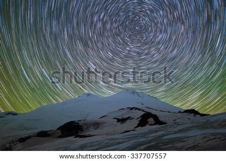 Star trails over Mount Elbrus - stock photo