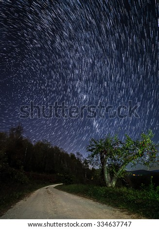 Star trails over the apple orchard in the Blue Ridge Mountains of North Carolina at night. - stock photo
