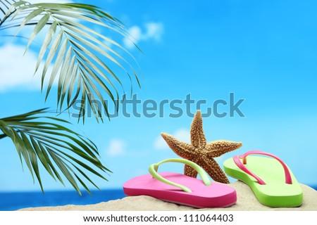 Starfish and flip-flops on sand beach. - stock photo