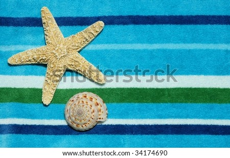Starfish and shell on striped beach towel, room for copy space - stock photo