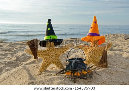 starfish on the beach with witch's hats and brooms - stock photo