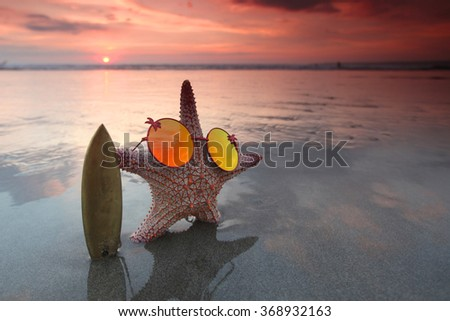Starfish surfer on the beach and beautiful sunset on Bali - stock photo