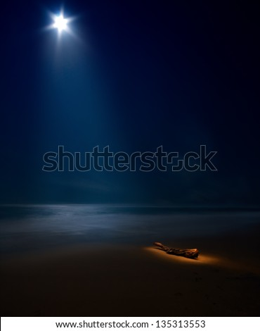 starry moon on night sea with beach and tree trunk painted with light with moon rays - stock photo