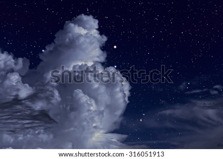 Starry night sky with some strong clouds - stock photo