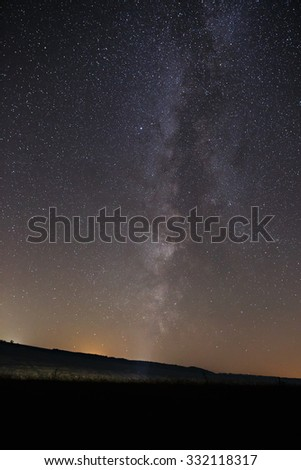 Starry sky and Milky Way on a background of hill. - stock photo