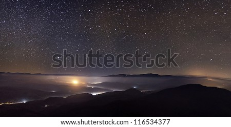 Starry sky over foggy mountains panorama with city lights below - stock photo