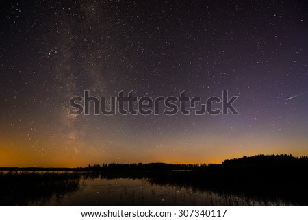 Stars and the Milky Way in the sky over the lake - stock photo