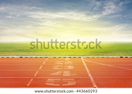 Start and Finish point of race track ,Running track number in front of tracks in stadium with beautiful green grass with blue sky scenery  background - stock photo
