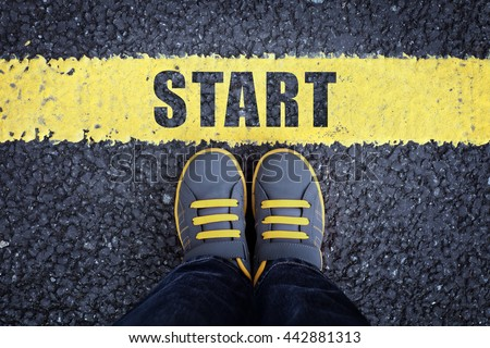 Start line child in sneakers standing next to a yellow starting line - stock photo