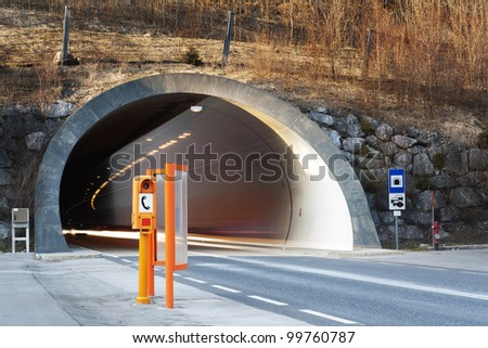 start of a conrete tunnel with fading lights of traffic and orange emergency telephone booth - stock photo