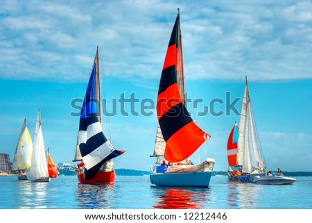 Start of a sailing regatta, fully crewed yachts with sails catching the wind, blue sky and white clouds on background. - stock photo