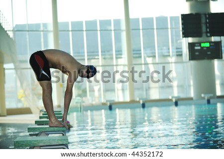 start position race concept with fit swimmer on swimming pool - stock photo