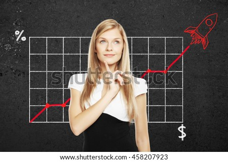 Start up concept with pretty thoughtful businesswoman. Business chart with red rocket ship on concrete wall in the background - stock photo