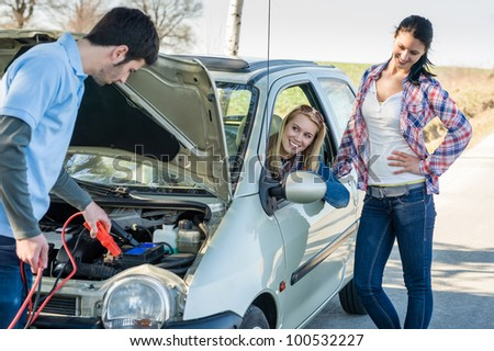 Starter cables man help to repair car two female friends - stock photo