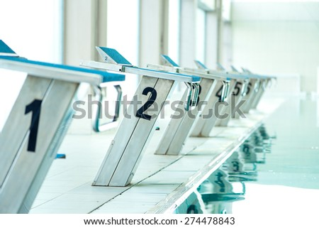 Starting blocks in row by the swimming pool, selective focus, toned image - stock photo
