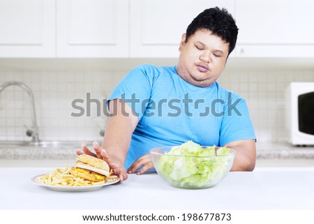 Starting healthy eating; overweight person rejects junk food - stock photo