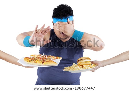 Starting healthy eating; overweight person says no to eat junk food - stock photo