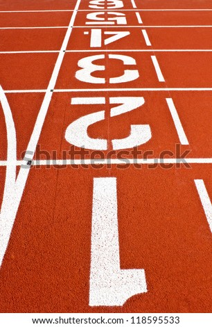 Starting line on a red running track at stadium - stock photo