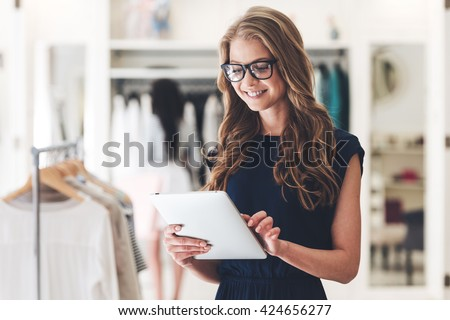 Starting new business. Beautiful young woman using digital tablet with smile while standing at the clothing store  - stock photo