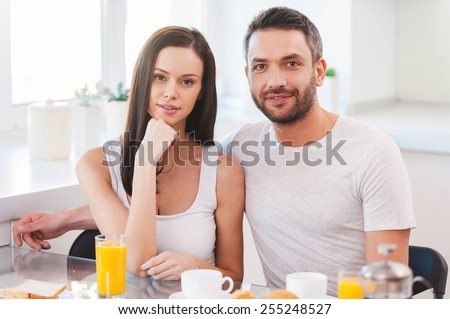 Starting new day together. Beautiful young couple bonding to each other while sitting in the kitchen together and having breakfast - stock photo