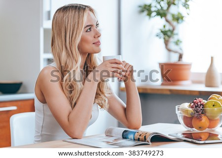 Starting new day with fresh coffee. Beautiful cheerful young woman holding coffee cup and looking away with smile while sitting at the kitchen at home - stock photo