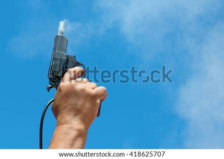 Starting pistol being fired.Hand firing a gun for starting race - stock photo