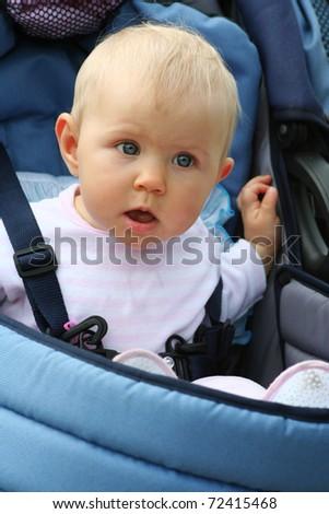 startled child in blue pram - stock photo
