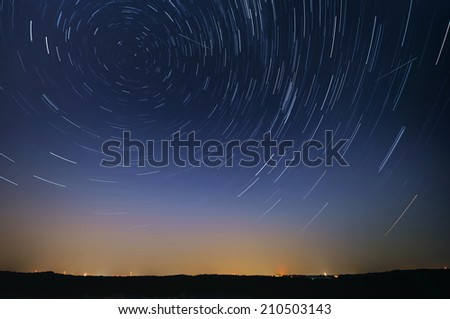 Startrail landscape of moving stars during the night of the Perseid meteor shower - stock photo