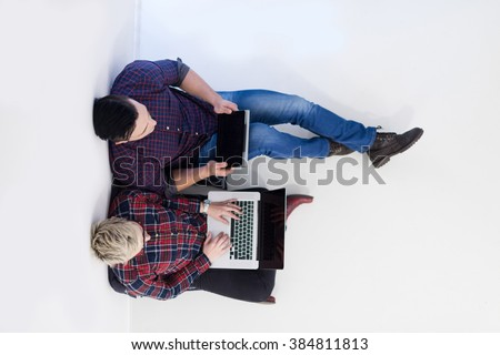 startup business and new mobile technology concept with  young couple in modern bright office interior working on laptop and tablet computer on new creative project and brainstorming, aerial top view - stock photo