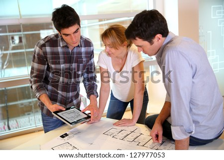 Startup business team working on blueprint - stock photo