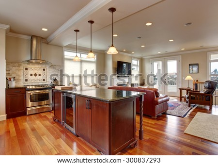 State of the art kitchen with deep stained cabinets, and stainless steel fridge. - stock photo
